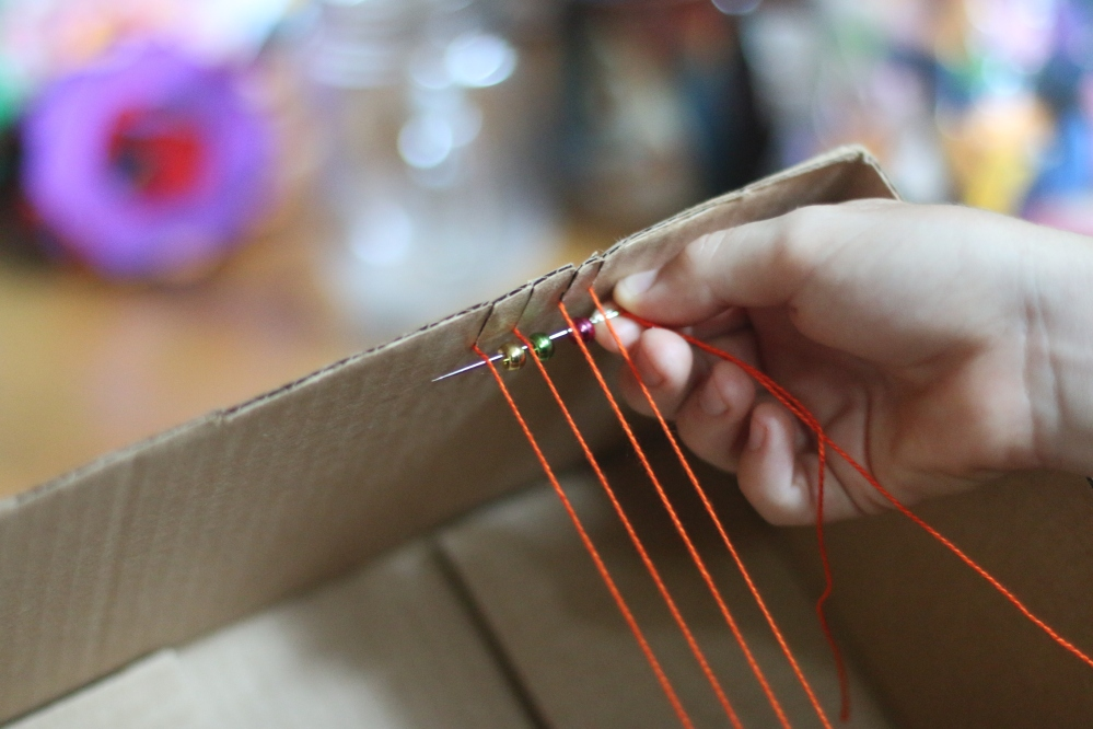 placing the bead needle underneath the threads on the loom to prepare to bead