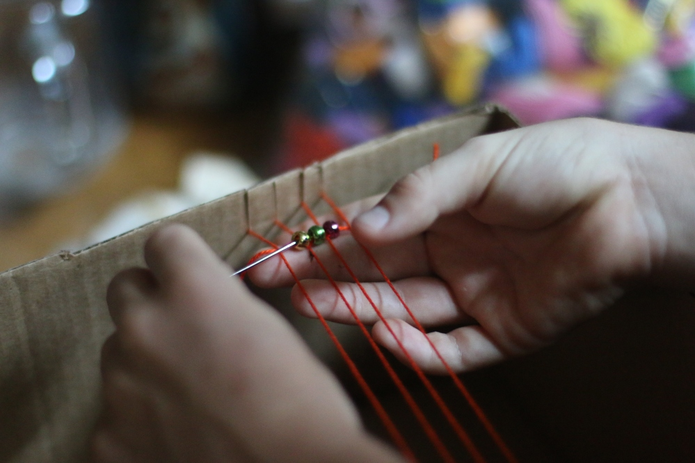 Pulling the thread through the first row of beads